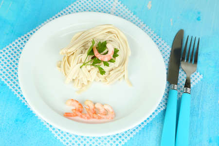 Pasta with shrimps on white plate, on wooden  photo