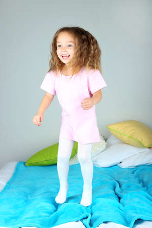 Little girl jumping on bed  photo