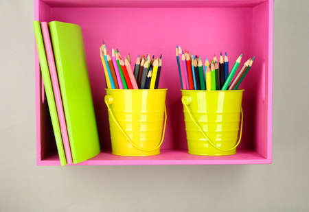 Colorful pencils in pails on shelf  photo