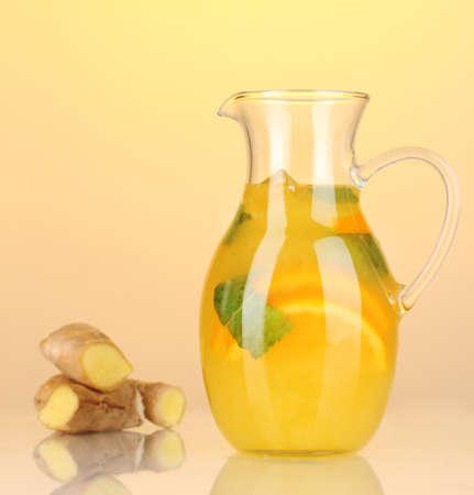 Orange lemonade in pitcher on yellow background photo