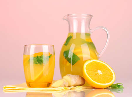 Orange lemonade in pitcher and glass on pink  photo