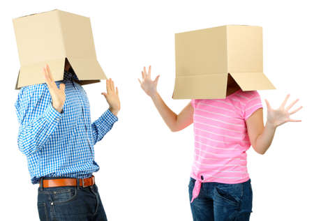 Couple with cardboard boxes on their heads isolated on white photo