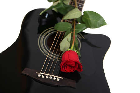 Acoustic guitar and red rose flower, isolated on white photo