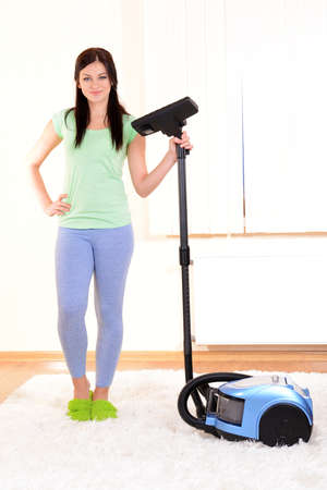 Beautiful young woman with vacuum cleaner in room photo