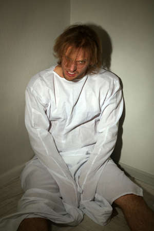 Mentally ill man in strait-jacket in room corner photo