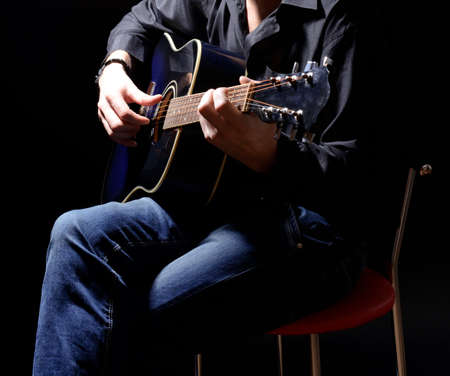 blues: Young musician playing acoustic guitar and singing, on dark