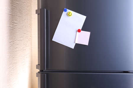 fridge: Empty paper sheets on fridge door Stock Photo