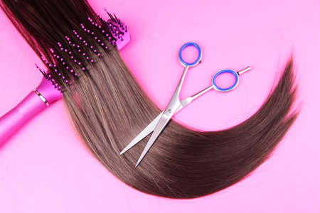 Long brown hair with hairbrush and scissors on pink  photo