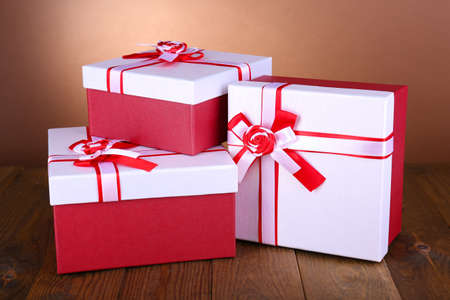 Beautiful gift boxes on table on brown  photo