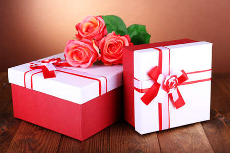 Beautiful gift boxes with flowers on table on brown  photo