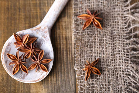 badian: Star anise in wooden spoon, on wooden background Stock Photo