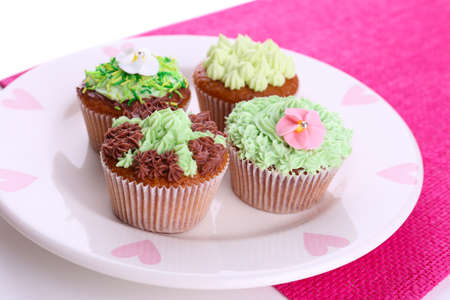 Tasty cupcakes with butter cream, on plate, on color napkin, close-up photo
