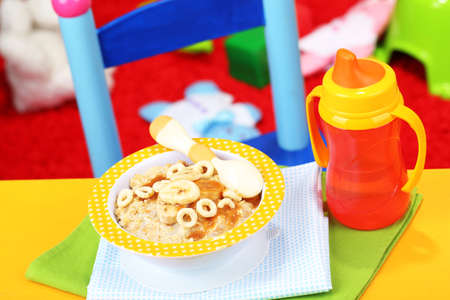 Bowl of porridge for baby and toys  on table, on toys background photo