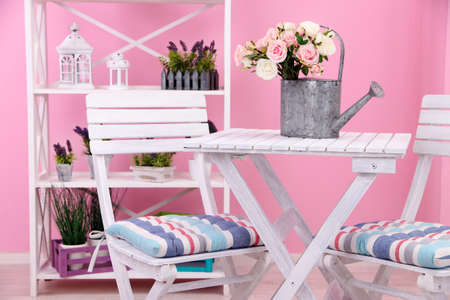 conjugation: Garden chairs and table with flowers on shelves on pink background Stock Photo