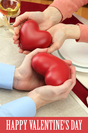 hands of romantic couple with hearts over a restaurant table  photo