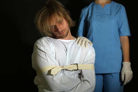 Mentally ill man in strait-jacket on black background photo