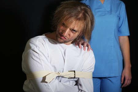 psychopath: Mentally ill man in strait-jacket on black background