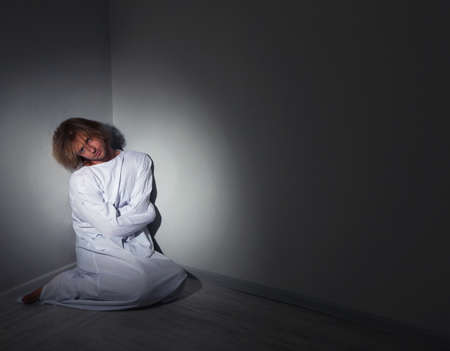 mentally ill: Mentally ill man in strait-jacket in room corner Stock Photo