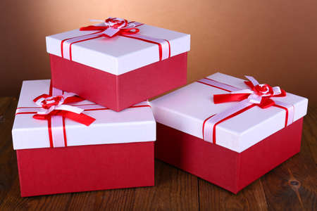 Beautiful gift boxes on table on brown background Stock Photo - 25216758