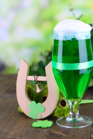 Glass of green beer and horseshoe for St Patricks day on wooden table close-up photo