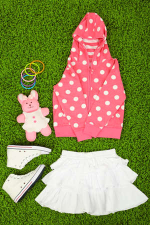Beautiful clothes for little girl  on green carpet photo