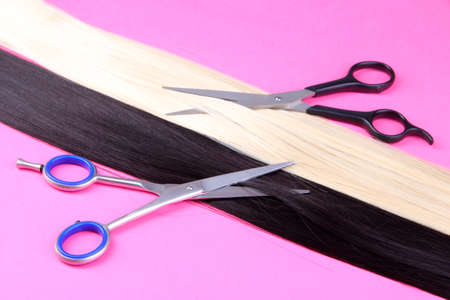 uncombed: Long black and blond hair with scissors on pink background Stock Photo