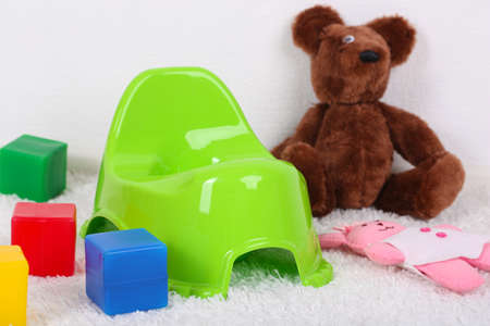 toy toilet bowl: Green potty on home interior background