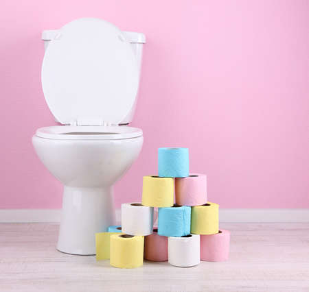 toilet brush: White toilet bowl and colorful rolls of toilet paper, in  bathroom