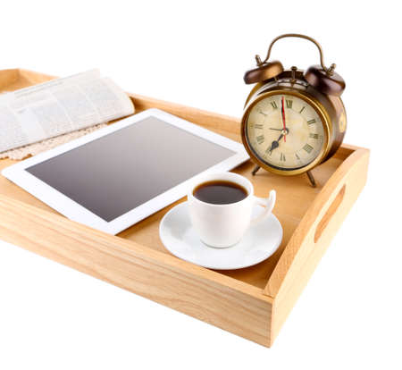Tablet, newspaper, cup of coffee and alarm clock on wooden tray, isolated on white photo