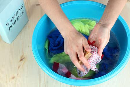 lavamanos: El lavado de manos en un recipiente de plástico sobre la mesa de madera de cerca