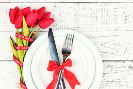 Romantic holiday table setting, on wooden background photo
