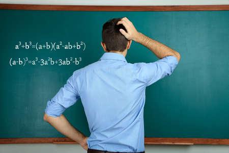 Young teacher near chalkboard in school classroom photo