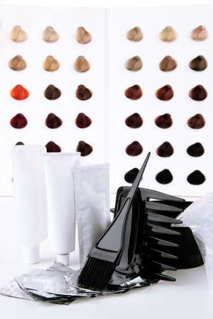 Hair dye kit on board with hair samples of different colors background photo