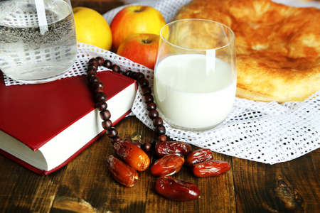 Composition with traditional Ramadan food, holy book and rosary, on wooden background