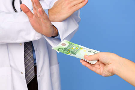 Male Doctor receiving money from patient, on blue background photo