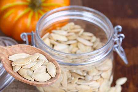 Pumpkin seeds in spoon and jar on table close up photo