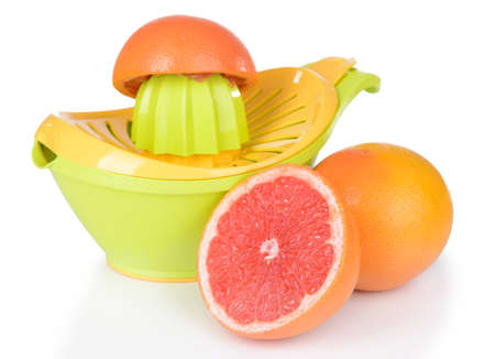 Citrus press and grapefruits isolated on white photo