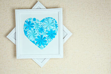 Beautiful handmade picture with heart from paper flowers on wall photo