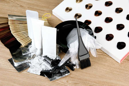 Hair dye kit and hair samples of different colors, on wooden background photo
