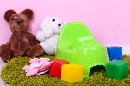 toy toilet bowl: Green potty on home interior  Stock Photo