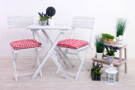 small garden: Garden chairs and table with flowers on wooden stand on white