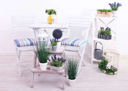 Garden chairs and table with flowers on wooden stands on white  photo