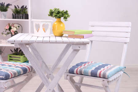 Garden chairs and table with flowers on shelves on white  photo