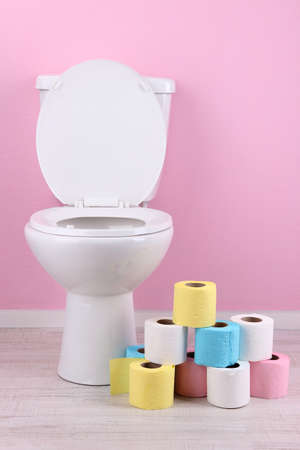 White toilet bowl and colorful rolls of toilet paper, in  bathroom Stock Photo - 25318020