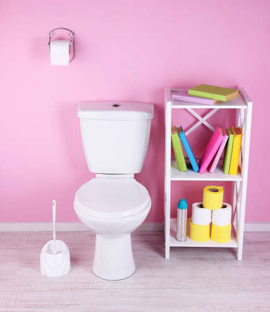 White toilet bowl and stand with books, on color wall  photo