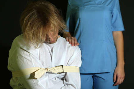 lunacy: Mentally ill man in strait-jacket on black background