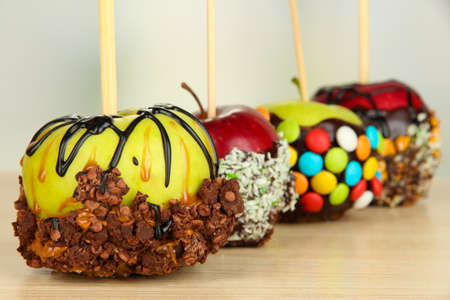 Candied apples on sticks on wooden table close up photo