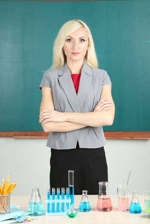 Chemistry teacher standing near table with tubes on blackboard background photo