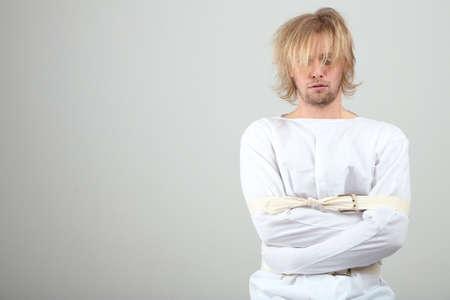 lunacy: Mentally ill man in strait-jacket on gray background