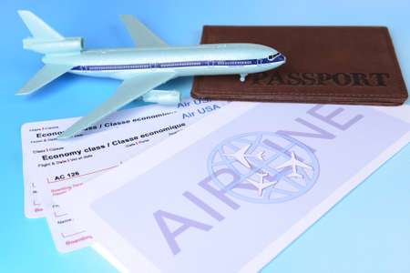 Airline tickets with passport on light blue background photo